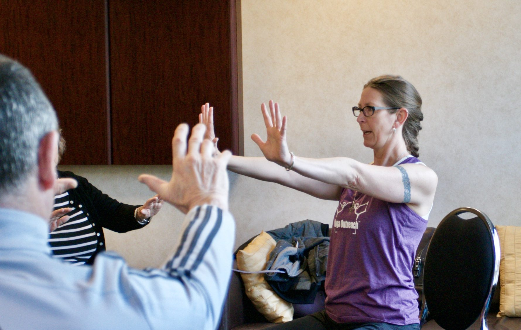 Yoga OUtreach volunteer instructor leading a class with seniors with early onset dementia