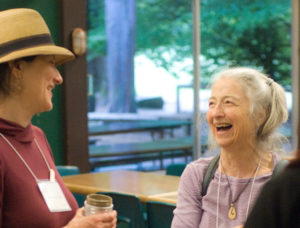 Two attendees share a laugh at Yoga Outreach's annual retreat.