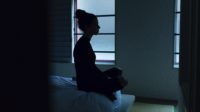Incarcerated teen girl sits on bunk practising mindfulness.