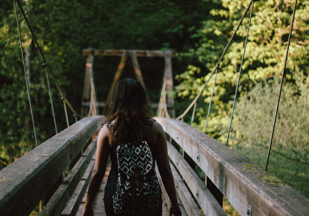 young woman with a back pack crossing a bridge into a forest
