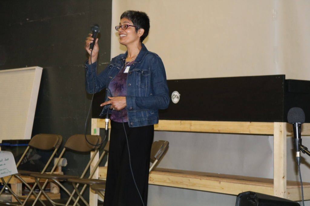 A woman of South Asian Descent with short hair, glasses, and a huge smile addresses a crowd from a stage, holding a microphone.