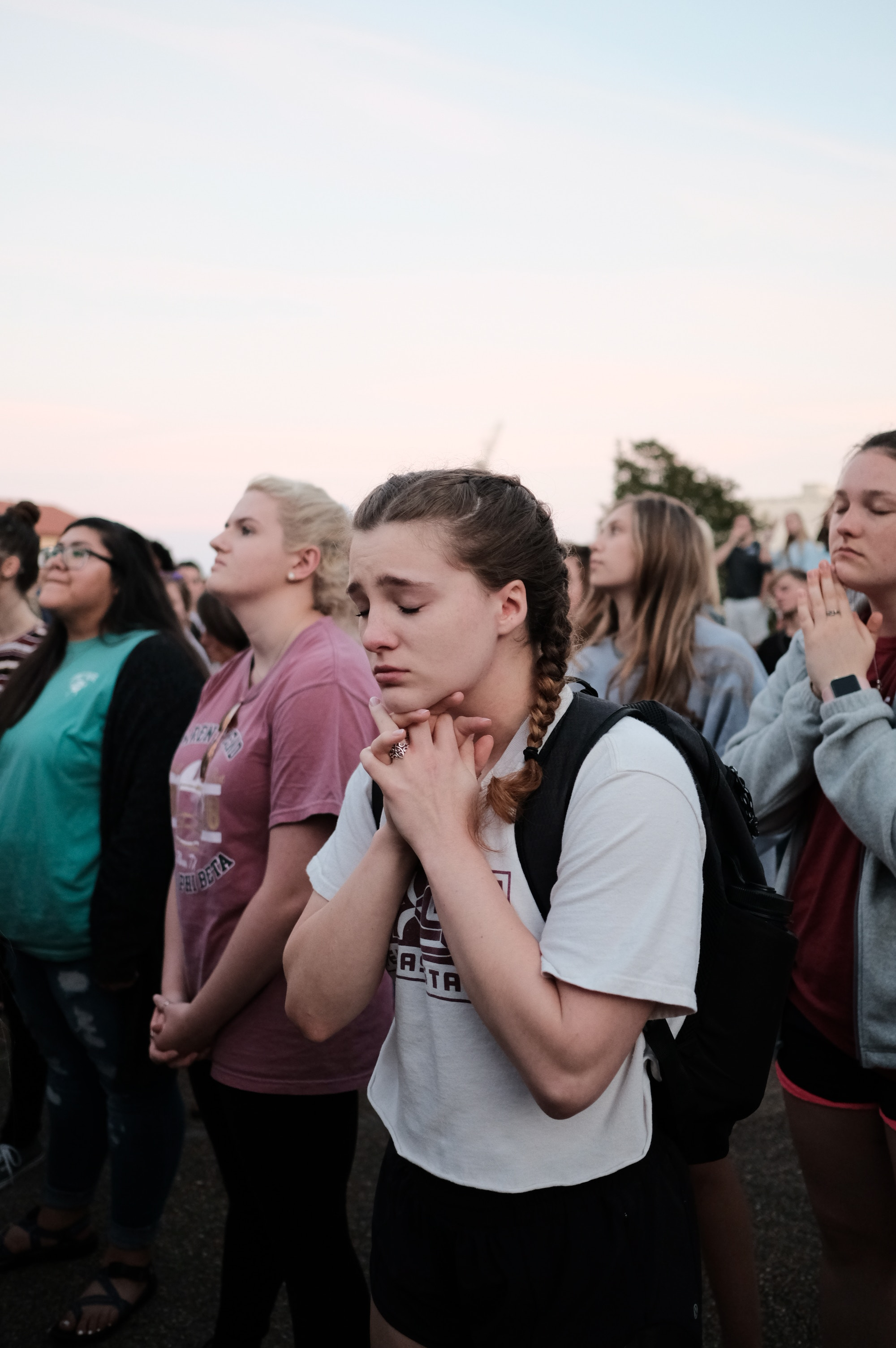 White girl clasps hands together, looking sad, at prayer meeting.