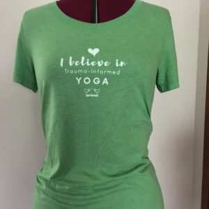 "green crew neck with the words ""I believe in trauma-informed yoga"" on it"