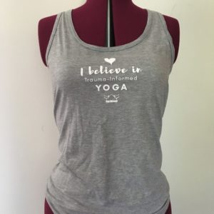 "Grey tank top with the words ""I believe in trauma-informed yoga"" on it"