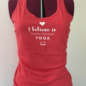 "red tank top with the words ""I believe in trauma-informed yoga"" on it"
