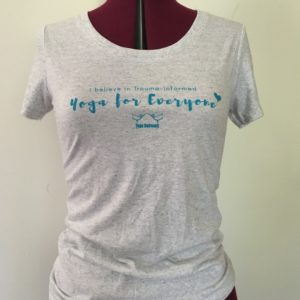"""white fleck crew neck with the words """"I believe in trauma-informed yoga"""" on it"""