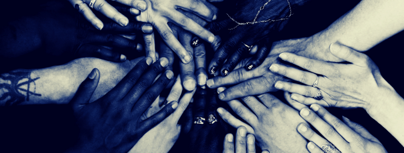 many hands of different ethnicities in a circle