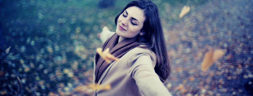 A young white presenting woman with long dark hair with her arms outstretched and her eyes closed enjoying the crisp autumn air as leaves fall around her.