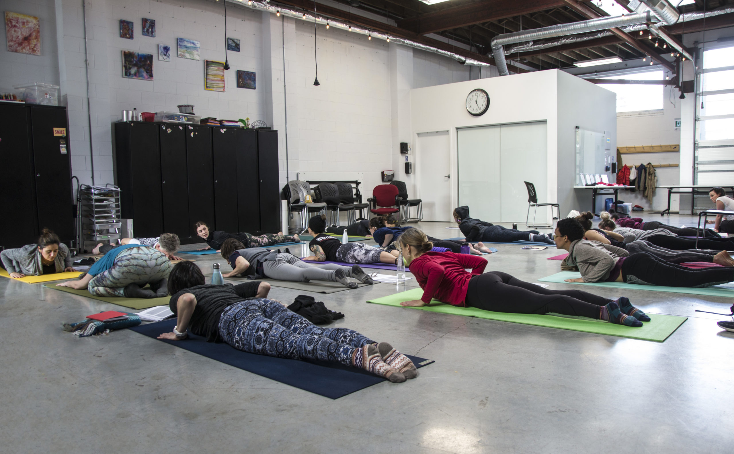 A trauma-informed yoga class - a group of student a on the floor on yoga mats. They are lying on their stomachs, hands planted at their sides at the waist, elbows up, they're chests and heads are raised in cobra form.