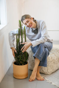 Hiro Demichelis a tall older white woman seated on a cushion hugging a tall cactus