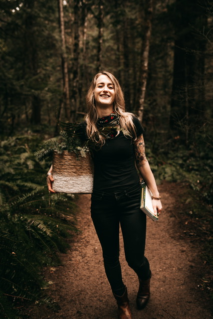 A white woman with long blond hair walking in the forest with a basket of fir boughs and a book in her hands.